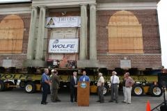 Leg. Rob Calarco at the podium speaking to the crowd that has come to see the historic Carnegie Library moved by Wolfe House & Building Movers of Bernville, Pa. Pictured to left of Leg. Calarco is County Executive Steve Bellone; to the right is Patchogue Mayor Paul Pontieri and village trustees.