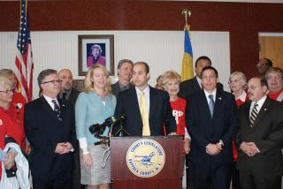 Leg. Rob Calarco at the podium discusses passage of his bill, IR 2025, requiring county roadways to be designed to accommodate all users. (left to right) Legislators Wayne Horsley and Kara Hahn (a co-sponsor of the bill); Leg. Calarco, Will Stoner of the AARP; Leg. Ricardo Montano. (Rear left to right) Eric Alexander of Vision Long Island; Sal Russo, 2nd vice president of SCAME; and Leg. William (Doc) Spencer.